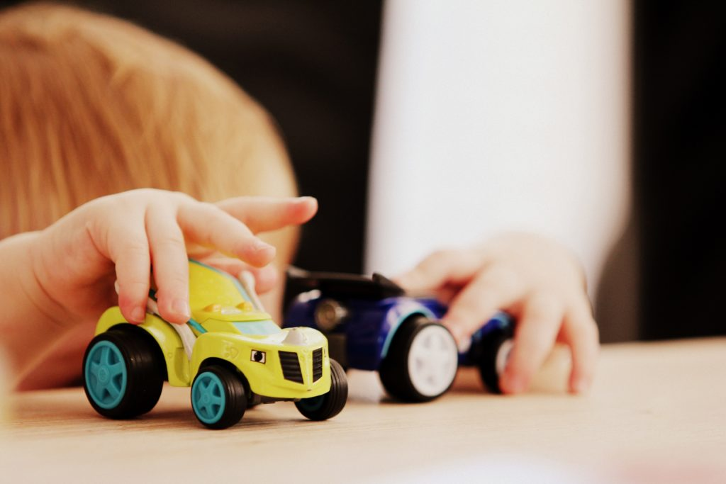 small boy playing with toy trucks